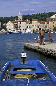 Children playing on the jetty in a small harbour on the island of Zlarin, Croatia.  -  James Boyd