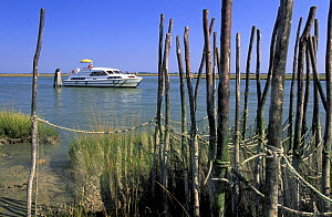 "Motoryacht behind nets (seraie) used on some of the islands in the Venetian lagoon. Venice, Italy. ^^^These islands are called �barene"". During certain periods when the tides are extremely high they a...  -  Roberto Rinaldi"