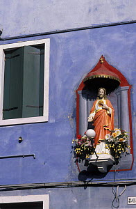 Statue of Jesuson the outside wall of a purple house, Burano, Italy.  -  Roberto Rinaldi