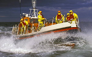 Crew of the Courtmacsherry, Ireland Lifeboat on the foredeck as she crashes through heavy seas. Designed to lie afloat at deep water moorings or at berth. The sheerline sweeps down for ease of survivo... - Rick Tomlinson