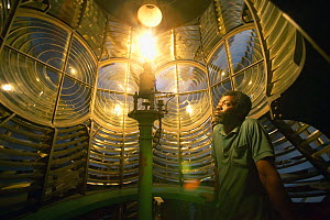 Lighthouse keeper watching the kerosene fueled light of Elbow Cay lighthouse in the Abacos Islands, Bahamas. - Onne van der Wal