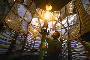 Man lighting the kerosene fueled light of Elbow Cay lighthouse in the Abacos Islands, Bahamas. - Onne van der Wal