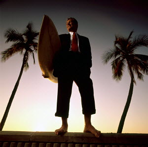 Businessman with surfboard on a Fort Lauderdale beach, Florida 1998. (Model released)  -  Gary John Norman