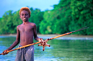 Young boy with fishing spear and starfish, New Ireland, Papua New Guinea  -  Roberto Rinaldi