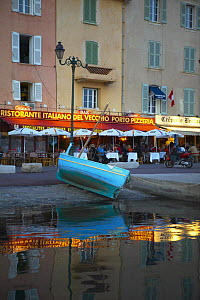 Boat pulled up outside waterside cafes in the port of St Tropez, South France.  -  Onne van der Wal