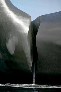 Water pouring from a smooth black iceberg, South Georgia. - Onne van der Wal