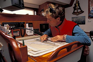 Man navigating with chart and parallel rule on a table in the cabin of a yacht.  -  Onne van der Wal