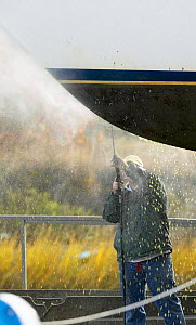 Pressure washing a cruising yacht at the end of the season.  -  Onne van der Wal