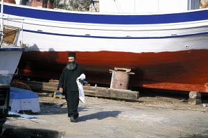 Greek Orthodox priest walking among fishing boats along the harbour of Vathi, on the island of Kalimnos, Dodecanese Islands, Greece - Daniel Allisy
