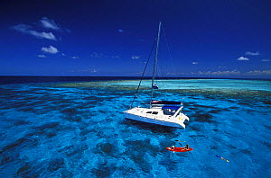 Kayaking from a cruising yacht in clear waters, Belize. Property Released.  -  Onne van der Wal