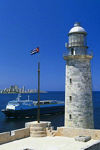 The lighthouse at the entrance to Havana Harbour with a ship cruising past, Cuba.  -  Onne van der Wal
