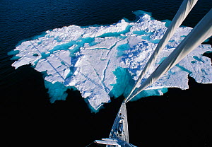 Mast view of 88ft sloop superyacht ^Shaman^ approaching a large iceberg, Spitsbergen, Svalbard, Norway. Property Released.  -  Onne van der Wal