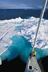 """Mast view of the crew of 88ft sloop superyacht """"Shaman"""" watching from the bow as the yacht approaches a large iceberg, Spitsbergen, Svalbard, Norway.  -  Onne van der Wal"""