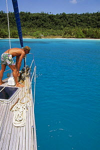 Man looking overboard at the lowering anchor aboard a cruising yacht off a sandy beach. - Onne van der Wal