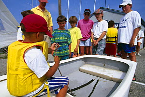 Children learing how to tie a figure of eight knot at a sailing school in Newport, Rhode Island, USA.  -  Onne van der Wal