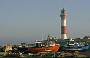 Buchanness lighthouse and boats pulled up onto the hard, North East Scotland. Spring 2005. - Philip Stephen