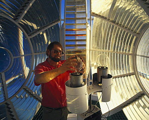 Changing the bulb inside the lens of a lighthouse.  -  Onne van der Wal