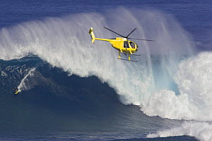 Helicopter filming tow-in surfer at Peahi (Jaws) off Maui, Hawaii.  -  David Fleetham