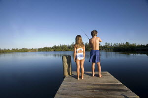 Boy, age 10, and a girl, age 8, fishing and playing at the end of a pier on Indian River, Vero Beach, Florida, USA 2003. Model released. - Gary John Norman