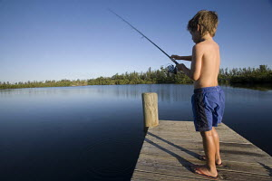 Little boy, age 10, fishing on a wooden jetty on Indian river Florida USA 2003. Model released. - Gary John Norman