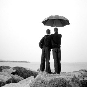 Two men standing on a rocky coast and looking out to sea from under an umbrella 2003. Model Released.  -  Gary John Norman
