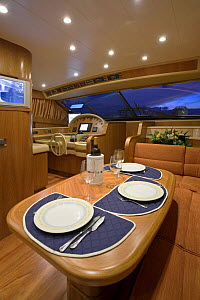 Table laid up for dinner in the seating and dining area, complete with flat screen television, of a luxurious Technema 65 motoryacht, built at the Rizzardi boatyard. Italy.  -  Angelo Giampiccolo