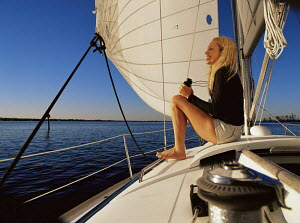 Woman with binoculars admiring the view of the ocean from her Beneteau 36s7 1998 first series cruising yacht was photographed off Vero beach Florida 2003. - Gary John Norman