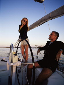 Couple enjoying a relaxing cruise at the helm of a Beneteau 36s7 1998 (first series) yacht off Vero beach in Florida 2003. - Gary John Norman