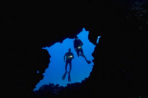 Divers pictured at the enterance to an underwater lava tube off the Island of Lanai, Hawaii.  -  David Fleetham