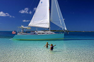 Shannon Shoalsailor moored with two children wading out to it. This innovative beachboat is a shallow draft boat designed to roam shallow waters such as these in Exuma, the Bahamas.  -  Onne van der Wal