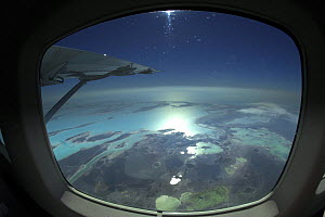 Aerial view through the window of a plane of the islands of Exuma, part of the chain of 365 islands that form the Bahamas.  -  Onne van der Wal