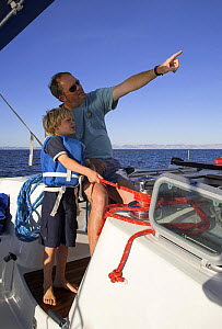 Father pointing something out to his son while on board a catamaran cruising to Isla San Francisco, Mexico. Model released.  -  Onne van der Wal