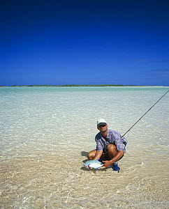 Fly fisherman holding a jack (Carangidae) in the shallow water of Rangiroa, French Polynesia.  -  Onne van der Wal