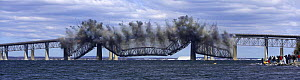 After simultanious explosions, the middle of the old Jamestown Bridge falls in to the water in Jamestown, Rhode Island, USA.  -  Onne van der Wal