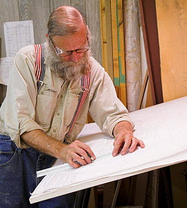 Man drawing out plans for a yacht under construction.  -  Onne van der Wal