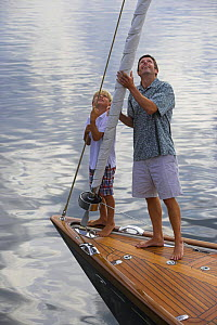 Father and son on the bow of a classic cruising yacht, checking the sails. Rhode Island.  -  Onne van der Wal