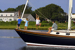 Young family playing the bow of a cruising yacht, Rhode Island.  -  Onne van der Wal
