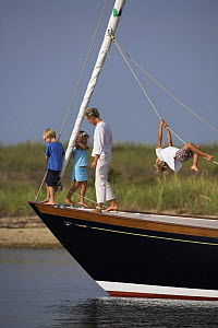 Young family anchored aboard a cruising yacht, with small boy swinging from the sheets. Rhode Island. Model released.  -  Onne van der Wal