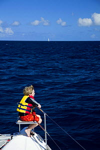 Young boy sitting in bow seat on the deck of a catamaran looking out to sea, British Virgin Islands, Caribbean. December 2006.  -  Onne van der Wal