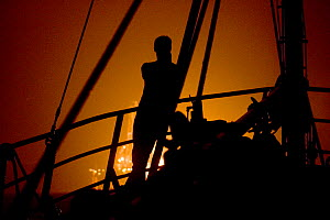 Fisherman on a trawler, watching an oil rig flaring off gas at night in the North Sea. September 2006. - Philip Stephen