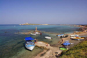 Boats and people on the shore of Portopalo di Capopassero (Siracusa) with the island of Capo Passero, the most southern point of the italian peninsula, in the background, Italy.  -  Angelo Giampiccolo