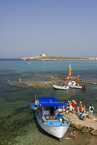 Tourists boarding a boat on the shore of Portopalo di Capopassero (Siracusa) with the island of Capo Passero, the most southern point of the italian peninsula, in the background, Italy.  -  Angelo Giampiccolo