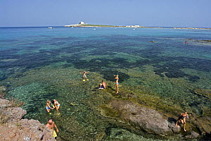 Tourists and locals swimming in the sea at Portopalo di Capopassero (Siracusa) with the island of Capo Passero, the most southern point of the italian peninsula, in the background, Italy. - Angelo Giampiccolo