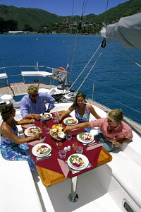 Guests on a charter sailing yacht dine on the aft deck during a cruise in the Caribbean. - Neil Rabinowitz
