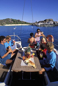 Guests onboard a charter sailing yacht dining on the aft deck during a Caribbean charter. - Neil Rabinowitz