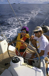 Watched by an adult a young boy helming a sailing yacht during a Caribbean charter. - Neil Rabinowitz