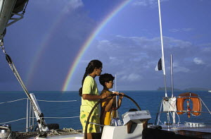 A double rainbow forms in the distance behind a young boy and an adult at the helm of a charter yacht during a cruise around the Society Islands in French Polynesia, South Pacific. - Neil Rabinowitz