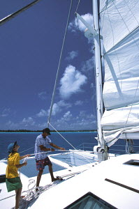 A young boy and an adult trimming the sails of a charter catamaran during a cruise around the Society Islands in French Polynesia, South Pacific. - Neil Rabinowitz