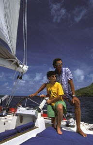 A young boy and an adult at the helm of a charter yacht during a cruise around the Society Islands in French Polynesia, South Pacific. - Neil Rabinowitz