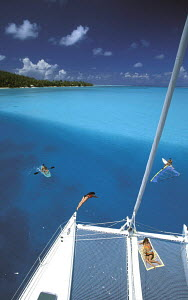 Guests kayaking, windsurfing, diving and sunbathing onboard a charter catamaran during a cruise around the Society Islands, French Polynesia, South Pacific. - Neil Rabinowitz